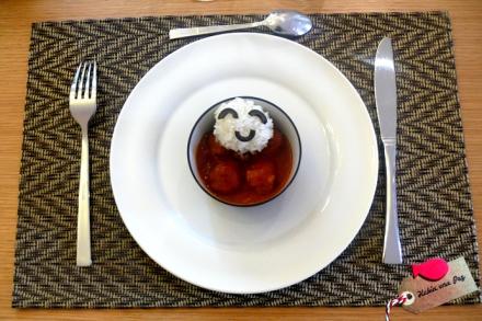 Receta infantil de carita feliz de arroz sobre albóndigas